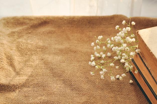 Weinlesefrühlingshintergrund mit weißen blumen, vergilbte alte bücher auf der leinwand.