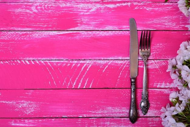 Weinlesegabel und -messer auf einer rosa holzoberfläche