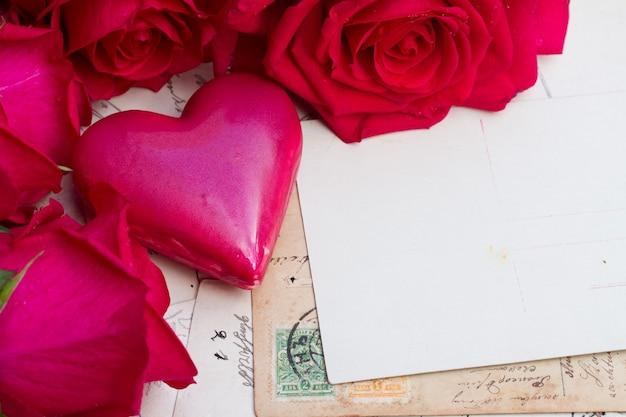 Weinlesehintergrund mit rosa herz und frischen rosen