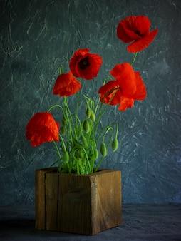 Weinlesehintergrund mit roten mohnblumen in einem hölzernen vase