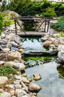 Weinleseholzbrücke über einem nebenfluss mit steinen in einem stadtpark.