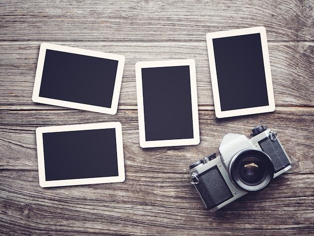 Weinlesekamera auf hölzernem hintergrund mit leeren fotorahmen