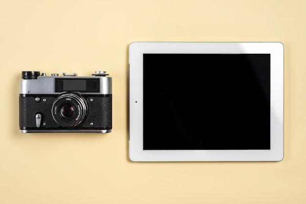 Weinlesekamera nahe der digitalen tablette mit leerer schwarzer bildschirmanzeige auf beige hintergrund