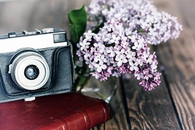 Weinlesekamera und blumenstrauß des lila frühlings blüht auf hölzernem bac