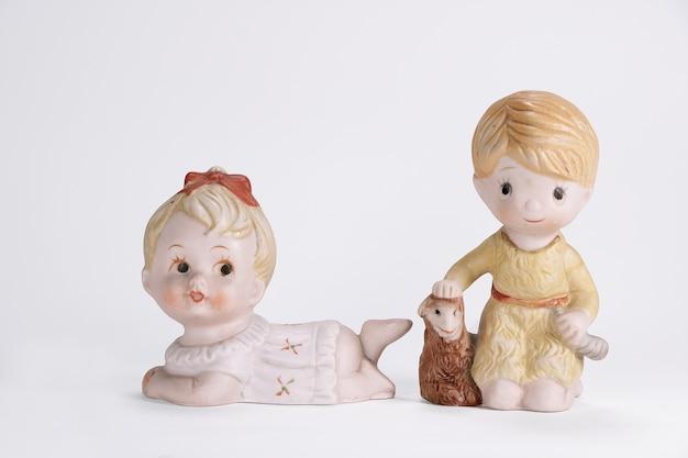 Weinlesekeramikpuppe des jungenschafs und des babymädchens für weißen hintergrund der innendekoration.