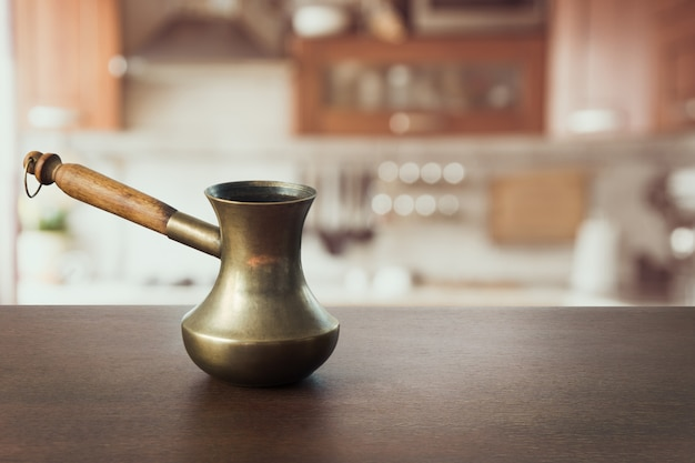 Weinlesekupfer cezve auf hölzerner tischplatte und moderner küche als hintergrund für anzeigenprodukte.