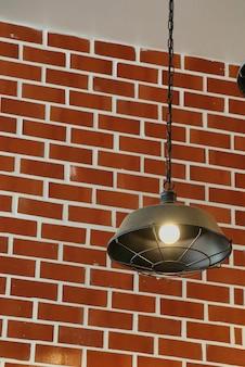 Weinleselampe, die von der decke mit licht auf der backsteinmauer hängt.