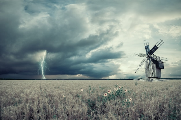 Weinleselandschaftslandschaft mit weizenfeldern und weinlesewindmühle, blitz und gewitter. filmfilter