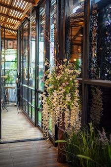 Weinlesemetallhaus mit glasfenster, verziert mit weißer orchideenblume und laminatboden