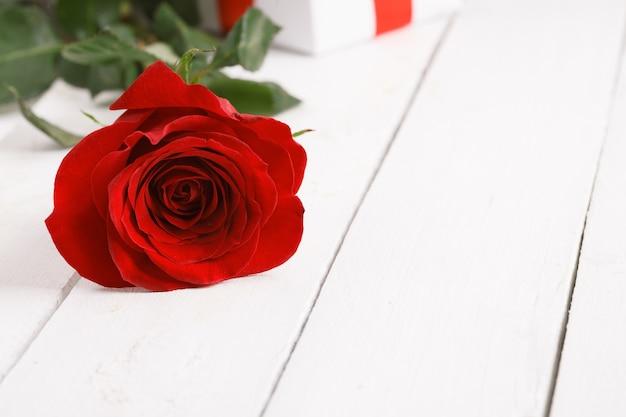 Weinleseoberfläche mit reizender rosenblume auf holztisch