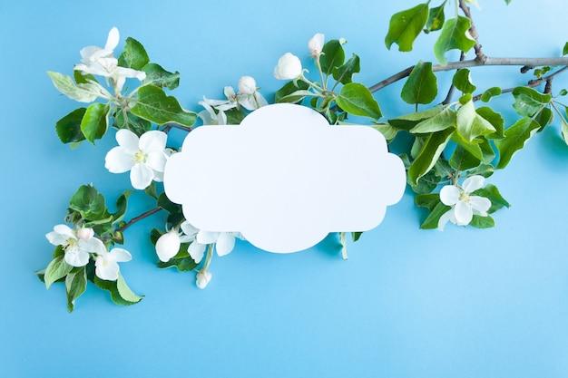Weinleserahmen mit blütenapfel auf blauem hintergrund