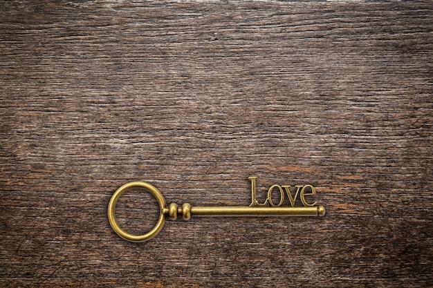 Weinleseschlüssel für liebe auf hölzernem hintergrund mit raum. valentinsgrußhintergrund.