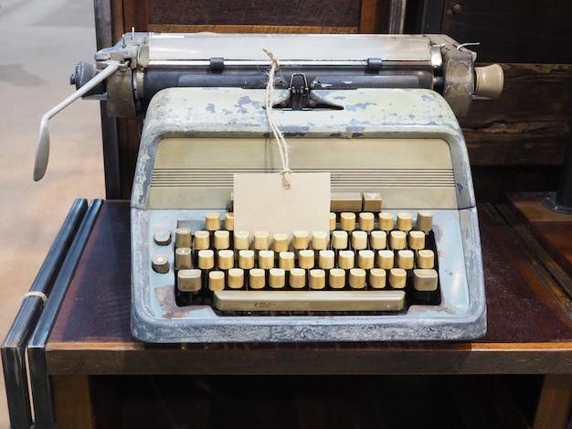 Weinleseschreibmaschine und markenaufkleber auf dem hölzernen schreibtisch