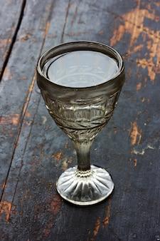 Weinleseschussglas mit wodka auf einer alten hölzernen schwarzen tabelle