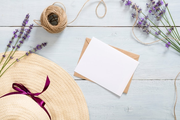 Weinlesestrohhut, kraftpapierumschlag, buchstabe, schnur, lavendelblume auf rustikalem blauem hölzernem schreibtisch