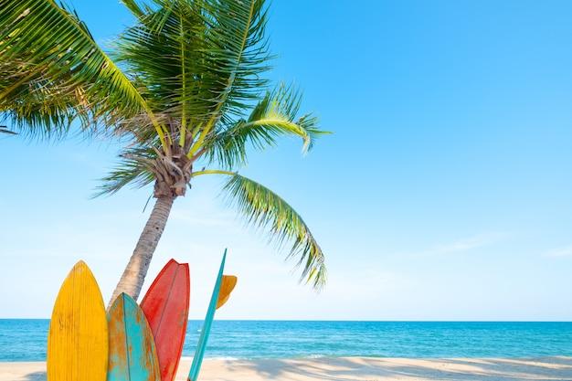 Weinlesesurfbrett mit palme auf tropischem strand im sommer