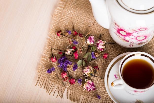 Weinlesetasse tee mit den knospen von rosen