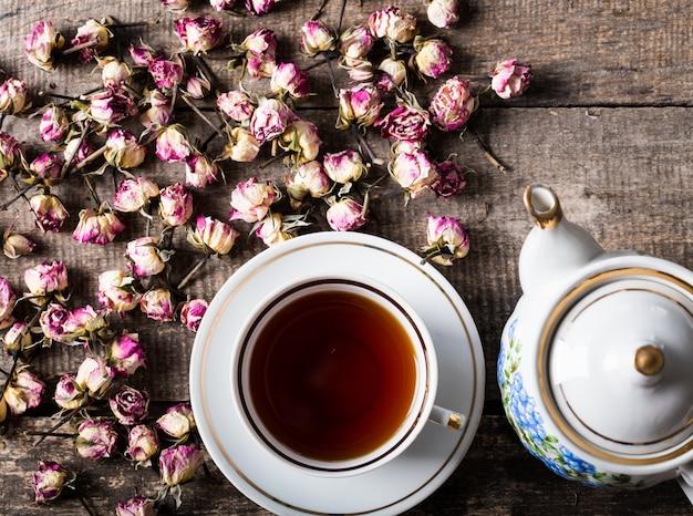 Weinleseteekanne und -schale mit blühendem tee blüht auf hölzernem hintergrund