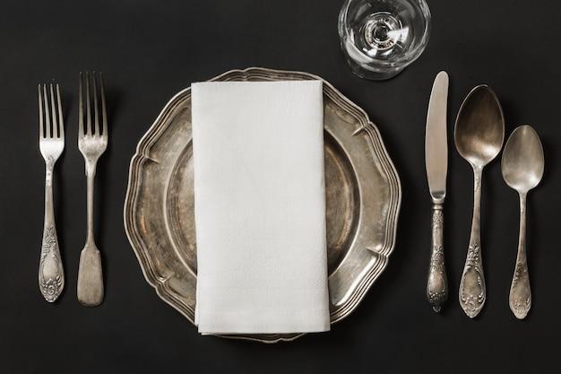 Weinleseteller mit tafelsilber für das mittagessen auf schwarzem. tischgedeck.
