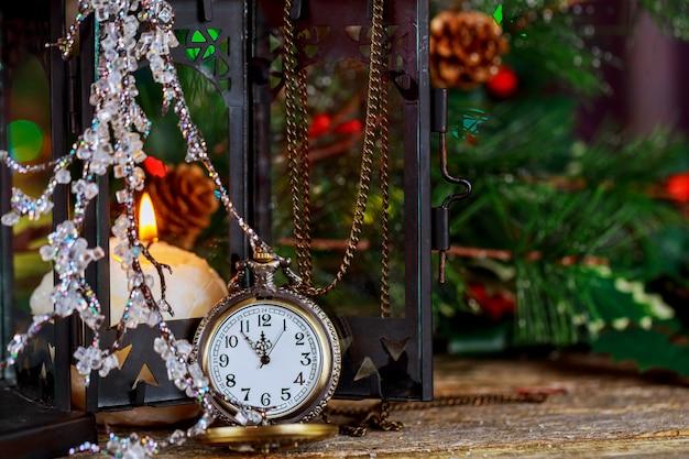 Weinleseuhr des weihnachten und des neuen jahres, die fünf bis mitternacht zeigt. brennende kerze des festlichen abends