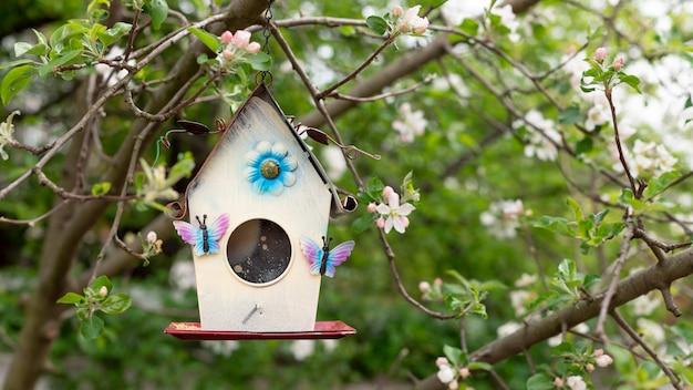 Weinlesevogelhaus an der wand eines blühenden apfelbaums. federwand