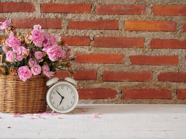 Weinlesewecker mit rosen im korb auf weißem holztisch