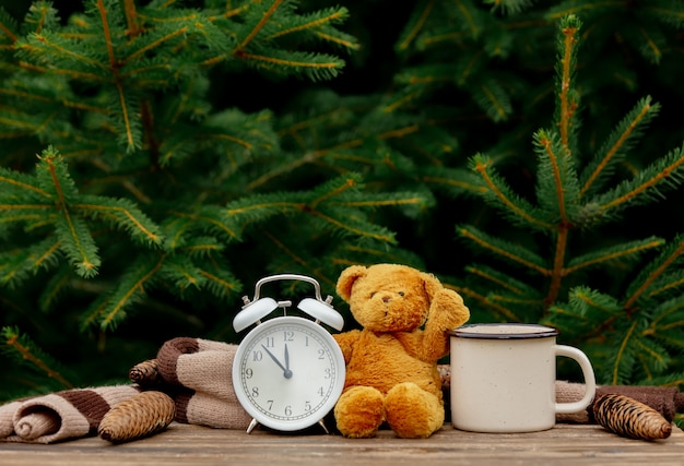 Weinlesewecker, teddybär und tasse kaffee auf holztisch mit fichtenzweigen auf hintergrund