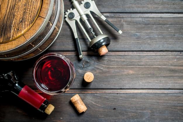 Weinoberfläche. ein fass rotwein mit einem korkenzieher. auf einer holzoberfläche.