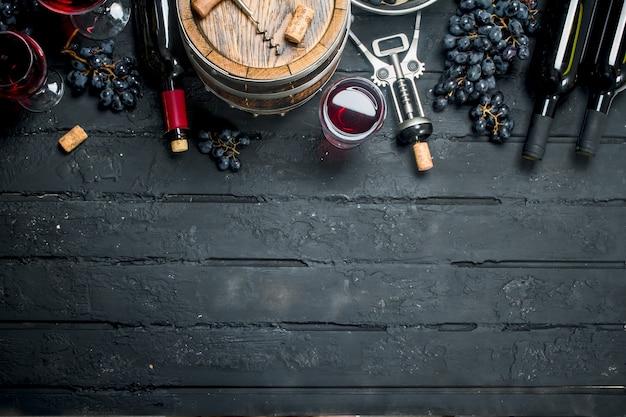 Weinoberfläche. rotwein mit trauben und einem alten fass. auf einer schwarzen rustikalen oberfläche.