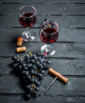 Weinoberfläche. rotwein mit trauben und korkenzieher. auf einer schwarzen rustikalen oberfläche.