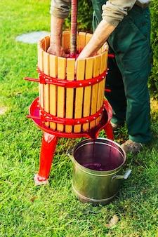 Weinpresse-maschine. junger mann, der wein mit hölzerner weinpresse-maschine herstellt. brecher auf gras im freien. trauben ernte. konzept des kleinen handwerksbetriebes. spezielle ausrüstung für die herstellung von wein, weinbereitung.