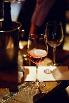 Weinprobe. auf dem holztisch steht ein mit rosa champagner gefülltes glas, ein eimer zum kühlen von flaschen