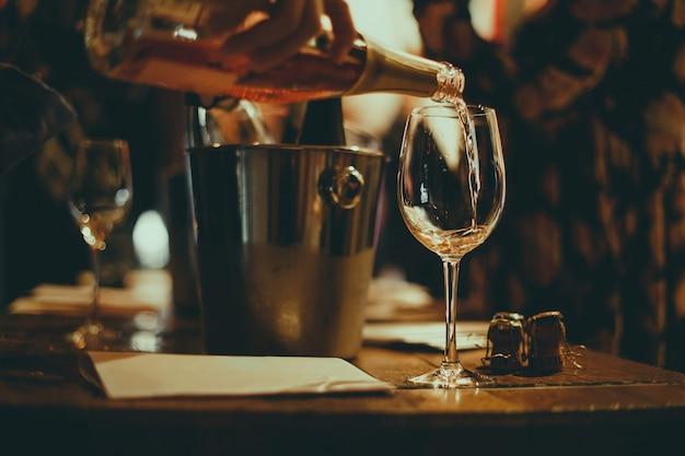Weinprobe: auf einem holztisch stehen silberne eimer zum abkühlen von weinen mit champagnerflaschen