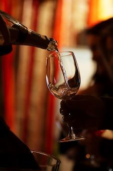 Weinprobe: pink champagner in gläser für besucher einschenken.