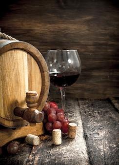 Weintisch. ein fass mit rotwein und frischen trauben. auf einem holztisch.