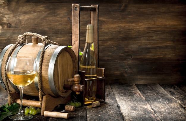Weintisch. ein fass weißwein mit zweigen grüner trauben. auf einem holztisch.