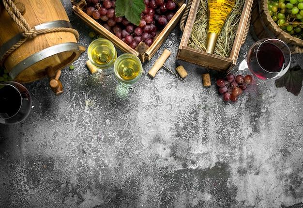 Weintisch. rot- und weißwein aus frischen trauben. auf einem rustikalen tisch.