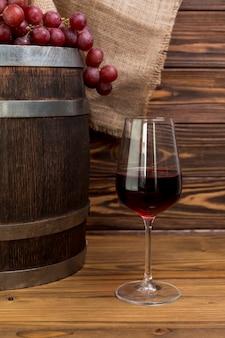 Weintraube auf hölzernem fass mit glas