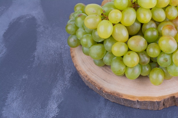 Weintrauben auf einem holzbrett auf blauer oberfläche