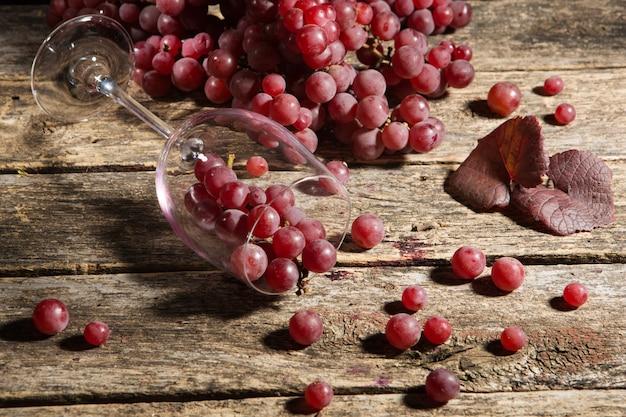 Weintrauben auf einem holztisch, weinglas wird umgeworfen, traubenbeeren werden über die oberfläche verstreut