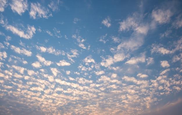 Weiß bewölkt mit blauem himmel. wellenwolken am himmel. flauschige wolke und sonnenuntergang.
