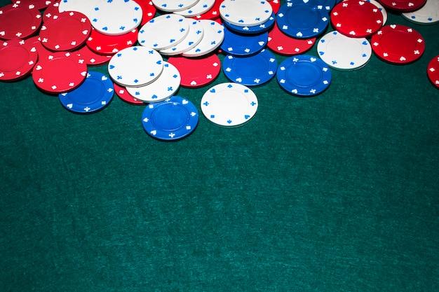 Weiß; blaue und rote kasinochips auf grünem hintergrund