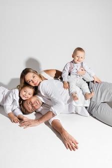 Weiß des fotostudios mit gladsome paar und ihren kindern, die sich auf dem boden entspannen und lächeln.