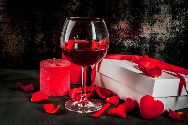 Weiß eingewickelte geschenkbox mit rotem band, rosafarbene blumenblumenblätter im weinglas, mit roter kerze auf dunklem steinhintergrund