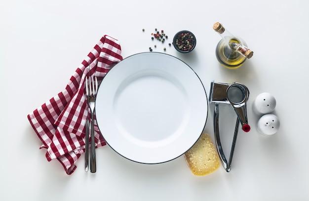 Weiß emaillierter leerer teller auf dem tisch mit einer rot karierten serviette und parmesan