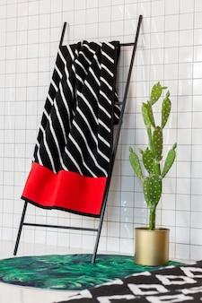 Weiß gefliestes badezimmer mit kaktus und treppe mit zebastreifenförmigem teddy-plaid mit rotem akzent
