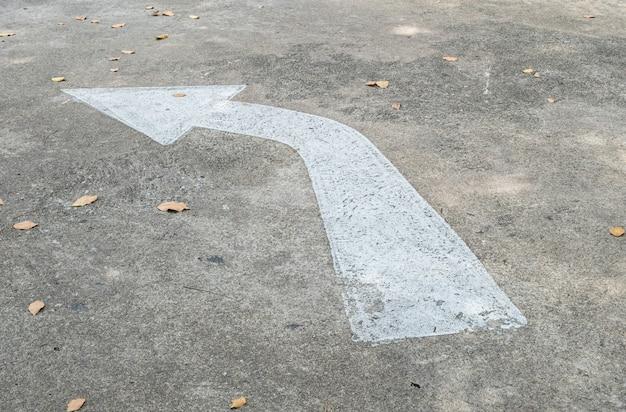 Weiß gemaltes pfeilzeichen der nahaufnahme auf zementstraßenbodenhintergrund