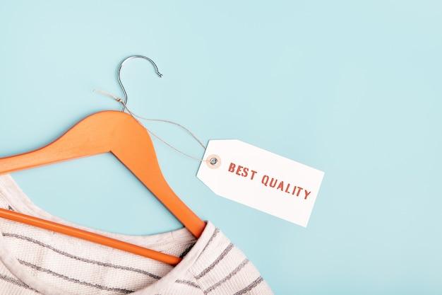 Weiß gestreiftes sweatshirt auf einem kleiderbügel und etikett mit der aufschrift best quality.