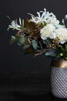 Weiß getönten blumenstrauß im vintage-stil in einer vase aus keramik auf dunkel