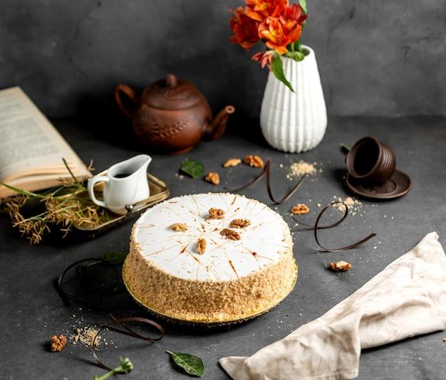 Weiß glasierter kuchen, verziert mit kuchenstreuseln und walnüssen